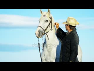 depositphotos_101553572-stock-video-male-cowboy-standing-with-white.mp4