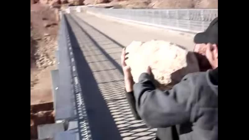 Бросают огромный камень с большой высоты в реку